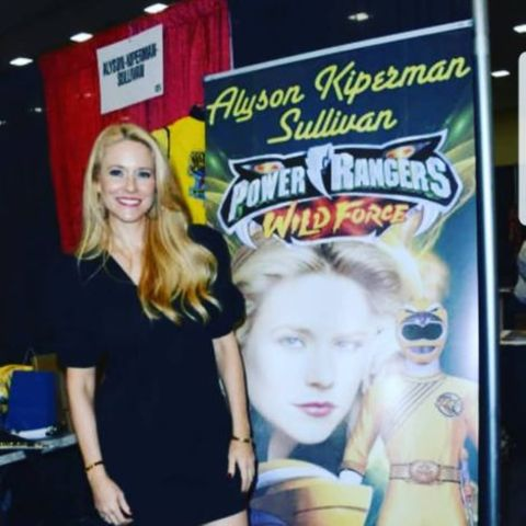 Alyson Kiperman in front of a flyer of herself at a Convetion