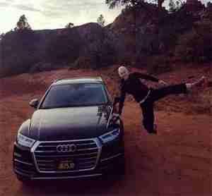 Ingrid Bolso Berdal posing besides her car