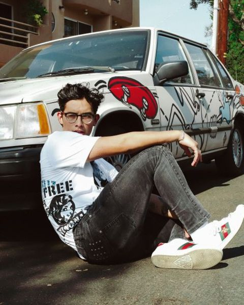 Brandon Arreaga posing in front of his car.