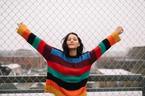 Fivel Stewart posing in LGBTQ themed sweater