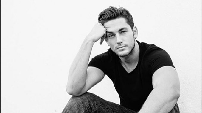 Brent Antonello in black t-shirt and black jeans poses for a photoshoot.
