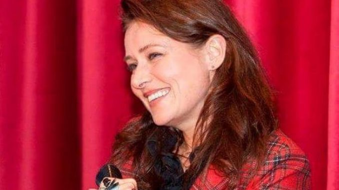Sidse Babett Knudsen in a red dress at a mic.