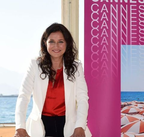 Sidse Babett Knudsen in a white coat and red shirt.