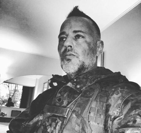 Louis Mandylor in army get up in black and white background.