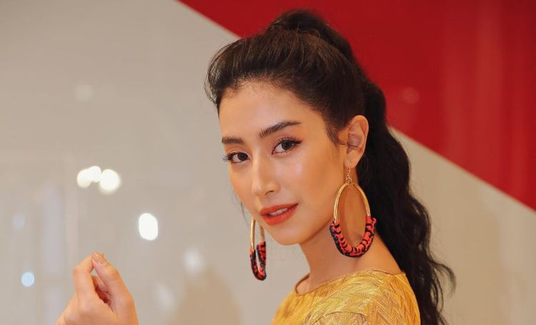 Chalida Vijitvongthong in a yellow dress looks at the camera.