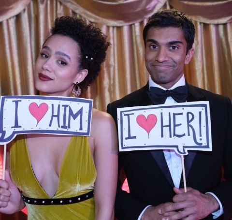 Nikesh Patel holding a I love her card to Nathalie Emmanuel in yellow dress, who holds I love Him card.