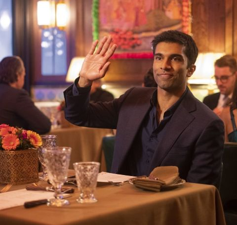 Nikesh Patel all suited up in a restaurant table.