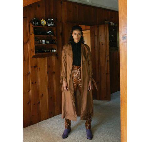 Laysla De Oliviera in a brown coat and pants.