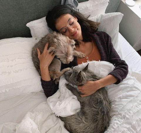 Laysla De Oliviera sleeping with two pets on her bed.
