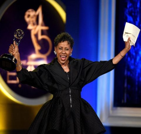 Vernee Watson-Johnson in a black dress celebrates on the stage with her Emmy award.