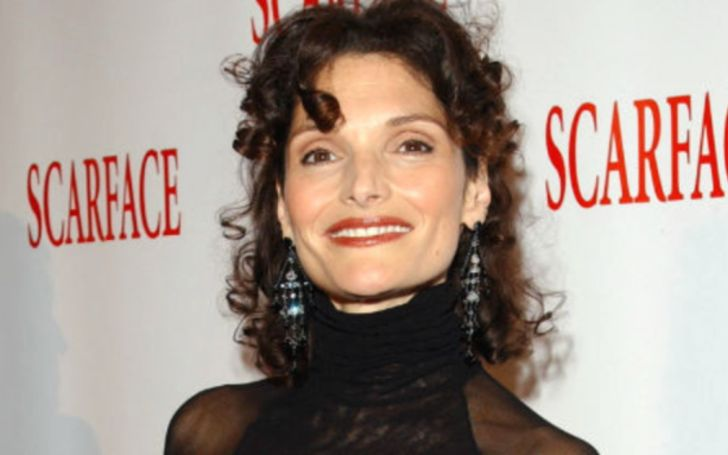 Mary Elizabeth Mastrantonio in a black sweater smiles at the camera.