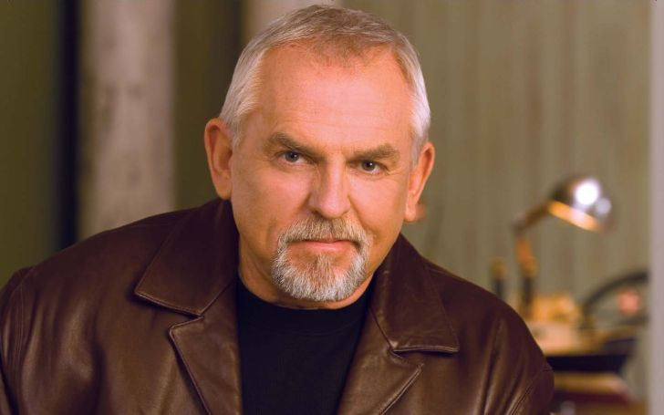 John Ratzenberger in a brown coat and black t-shirt.