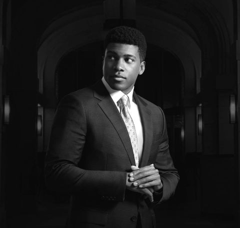 Eric Goree in a black suit in a black and white photo background.