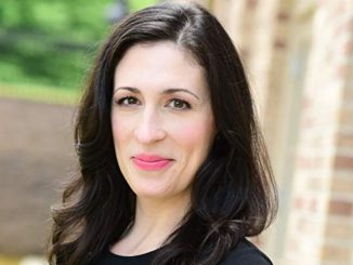 Cara Mantella in a black dress smiles at the camera.