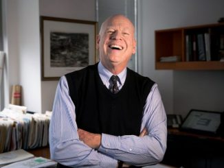 Knight Kiplinger laughing, while wearing a black half sweater