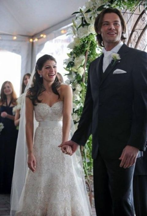 Genevieve Cortese holding the hand of her husband, Jared at their wedding.