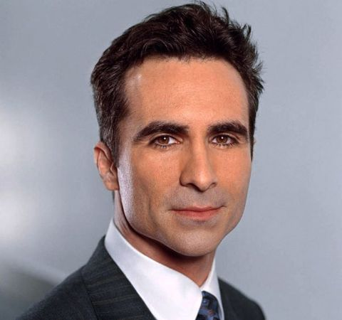 Nestor Carbonell in a black suit with black tie.