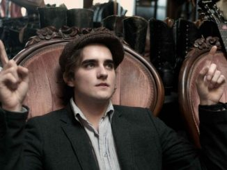 Landon Liboiron wearing a cap and a black suit.