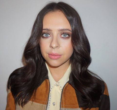 Bel Powley in a brown jacket looks at the camera.