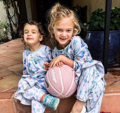 Two little girls dressed in similar clothes holding a pink basketball.