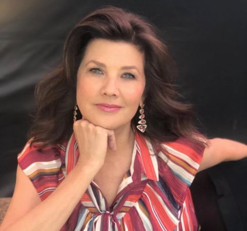 Daphne Zuniga in a red top poses for a photo.