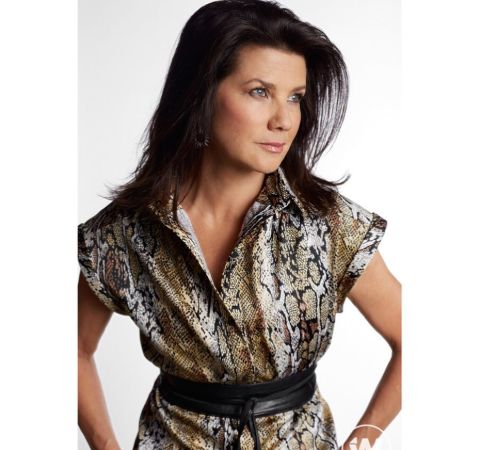 Daphne Zuniga in a brown dress at a photoshoot session.