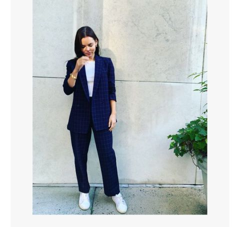 Eline Powell in a dark blue coat and dark blue pant.