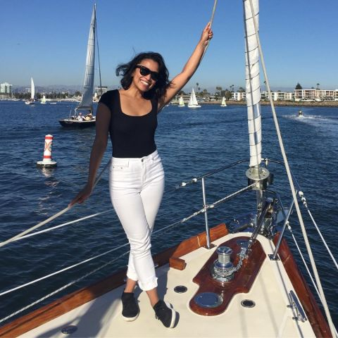 Pisay Pao in black t-shirt and white pant poses at a boat.
