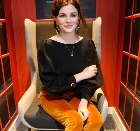 Aisling Bea in a black top and orange pant.