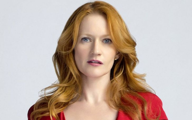 Paula Malcomson with auburn hair and blue eyes wearing a red dress.