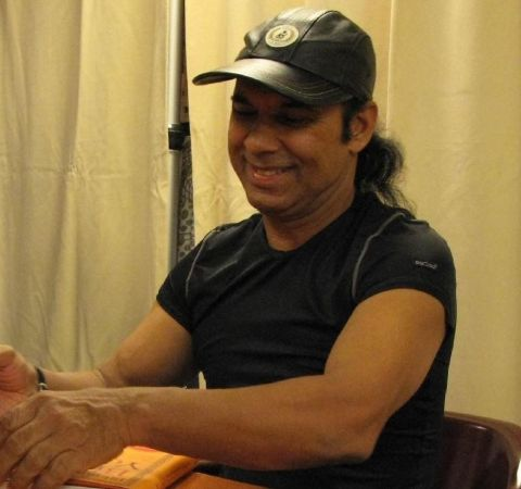 Bikram Choudhury in a black t-shirt and black cap.