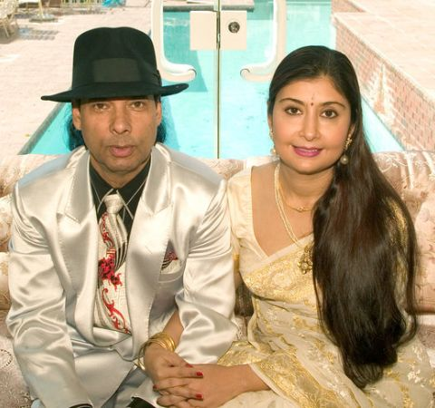 Bikram Choudhury in a silver suit with wife Rajashree Choudhury.