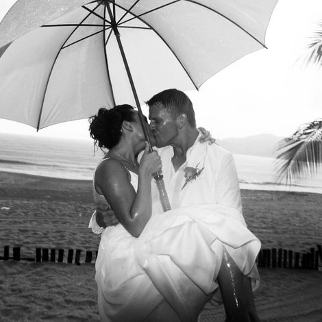 A man and woman Kissing under an umbrella.