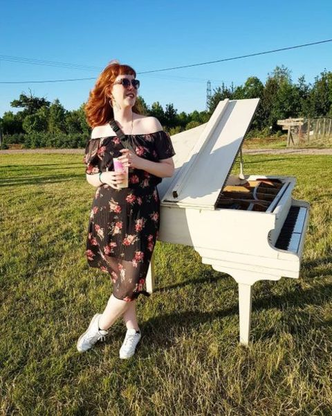 Singer, Josie Charlwood giving a pose while standing next to the white piano.