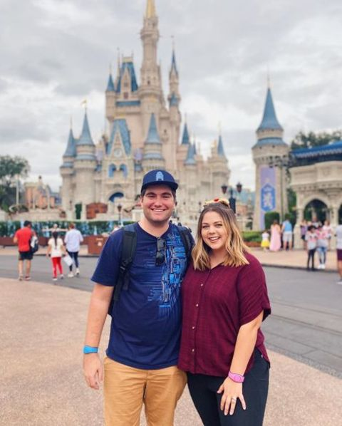 Sierra Schultzzie and her husband giving a pose in front of the famous Disney castle.