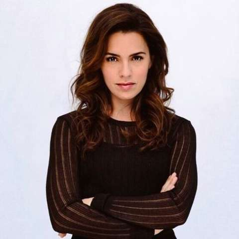 Actress, Melia Kreiling giving a pose in her black dress.