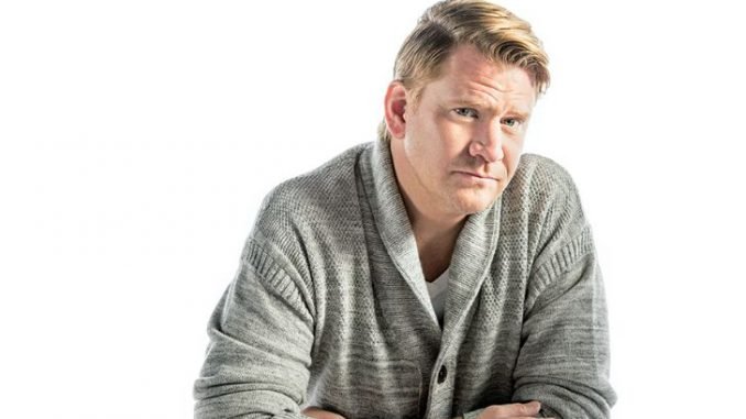 A man in his forties wearing a grey cardigan.