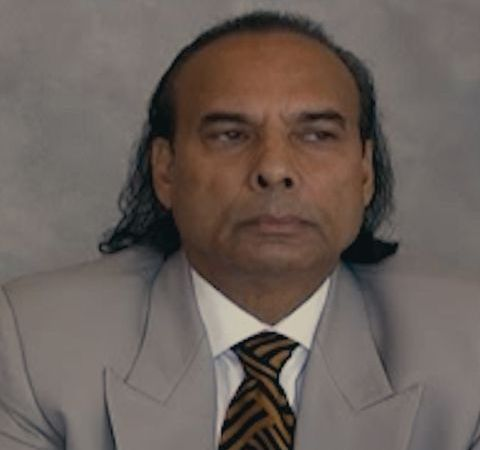Bikram Choudhury in a grey suit and brown tie.
