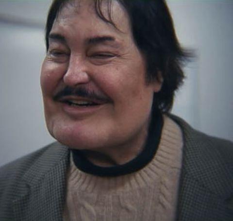 Robert Z'Dar smiles at the camera in a grey coat.