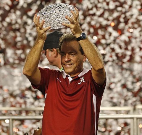 Nick Saban in a red t-shirt with a trophy on hand.