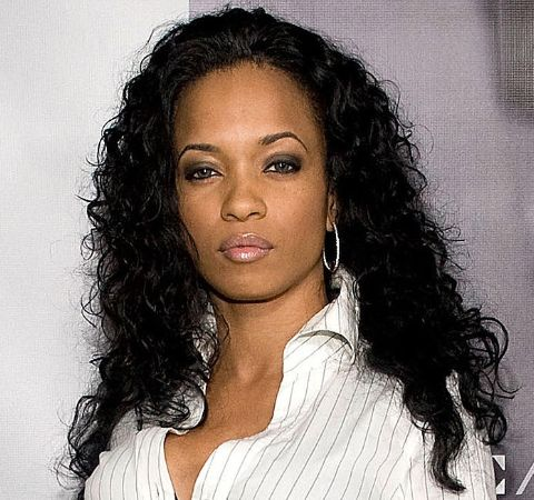 Karrine Steffans in a white shirt at a photoshoot.