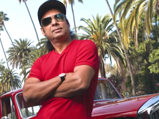 Bikram Choudhury posing in a red t-shirt and black cap.