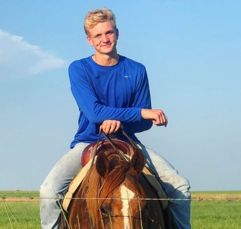 Ree Drummond's son Bryce Drummond in  blue t-shirt riding a horse.