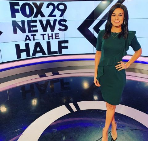 Shaina Humphries in a green dress poses at the sets of Fox 29 news.