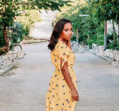Jeannette Reyes in a yellow dress poses for a picture in the local streets.