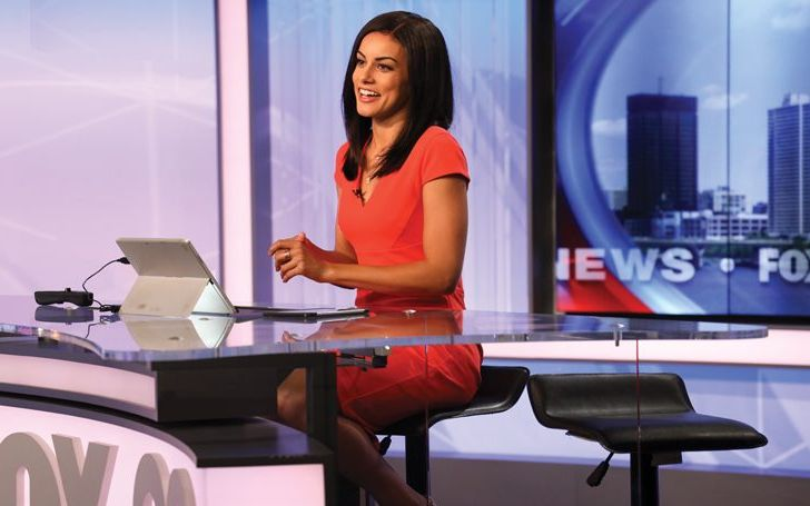 Shaina Humphries in a red dress reporting a news.
