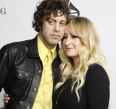 Jeremy Ivey in a black coat and yellow shirt with wife Margo Price.