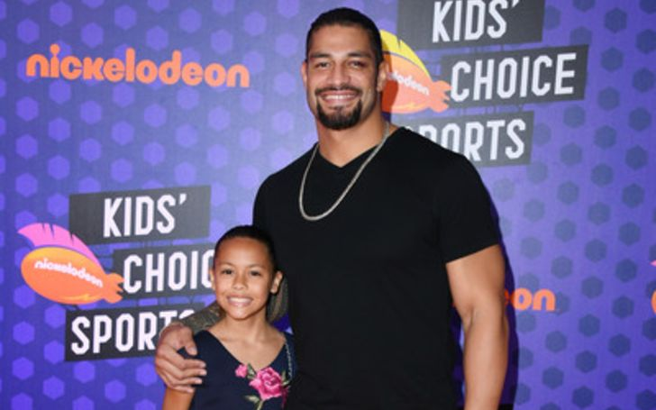 Joelle Anoa'i with her dad Roman Reigns in a black t-shirt.