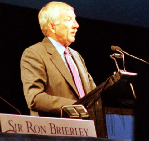 Sir Ron Brierley in a brown suit giving a speech.