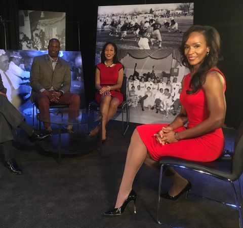 TaRhonda Thomas in a red dress interviewing several guests on the Action News.